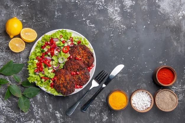 Bovenaanzicht smakelijke vleeskoteletten met salade en kruiden op grijze achtergrondfoto voedselmaaltijd
