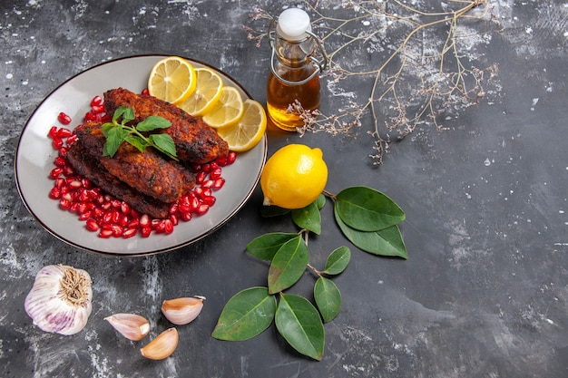 Bovenaanzicht smakelijke vleeskoteletten met schijfjes citroen op het grijze achtergrondschotelfoto voedsel