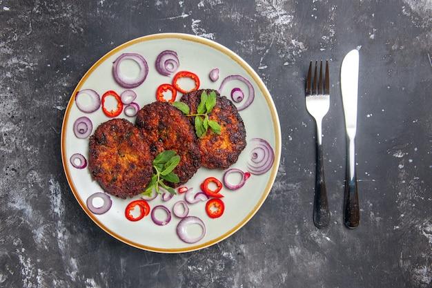 Bovenaanzicht smakelijke vleeskoteletten met uienringen op de grijze foto van de achtergrondmaaltijdkeuken