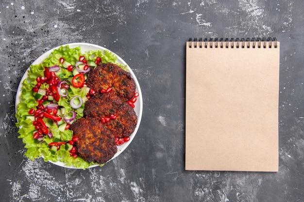 Bovenaanzicht smakelijke vleeskoteletten met verse salade op grijze achtergrondfoto vleesgerecht