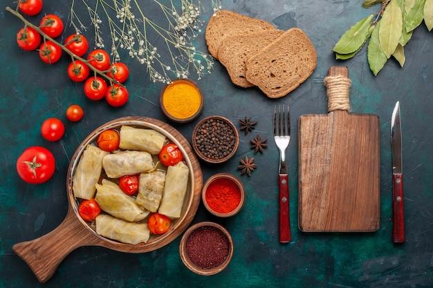Bovenaanzicht smakelijke vleesmaaltijd gerold in kool met brood en verse tomaten op het donkerblauwe bureau