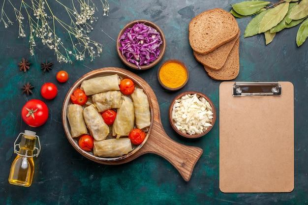 Bovenaanzicht smakelijke vleesmaaltijd gerold met kool en tomaten genaamd dolma met brood en olijfolie op donkerblauw bureau