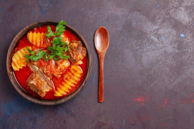 Bovenaanzicht smakelijke vleessaus soep met groenen en gesneden aardappelen op zwart