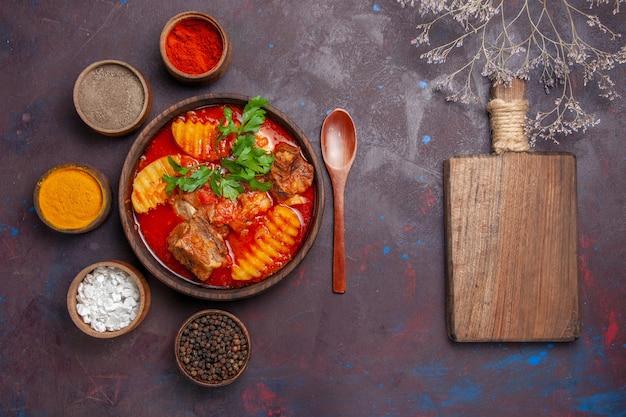 Bovenaanzicht smakelijke vleessaus soep met kruiden op zwart
