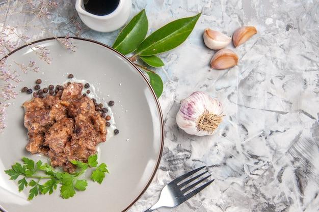 Bovenaanzicht smakelijke vleesschotel met saus op witte maaltijd dinerschotel