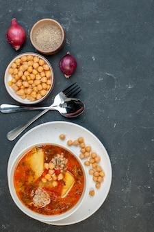 Bovenaanzicht smakelijke vleessoep bestaat uit aardappelen vlees en bonen op donkere achtergrond