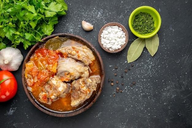 Bovenaanzicht smakelijke vleessoep met groen op een donkere vleeskleur grijze saus maaltijd warm eten aardappel foto diner schotel