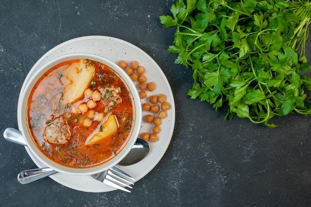 Bovenaanzicht smakelijke vleessoep met groene bonen en aardappelen op donkere achtergrond