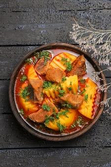 Bovenaanzicht smakelijke vleessoep met groenen en aardappelen op donker bureau