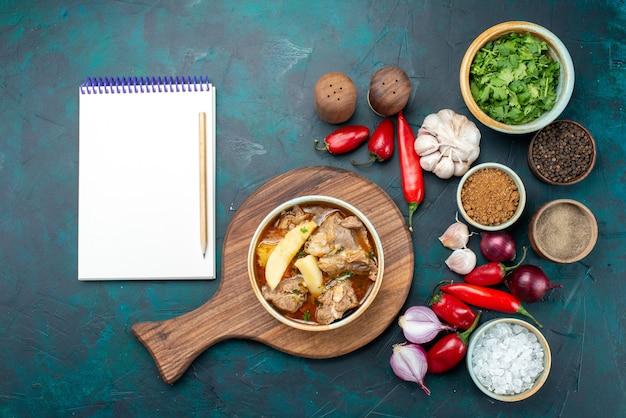 Bovenaanzicht smakelijke vleessoep met groenten gekookt samen met kruiden en verse groenten op het donkere bureau