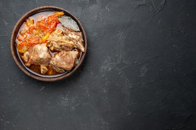 Bovenaanzicht smakelijke vleessoep met groenten op donkere saus maaltijdschotel warm eten aardappel kleurenfoto diner