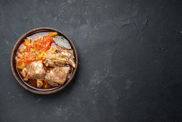 Bovenaanzicht smakelijke vleessoep met groenten op donkere saus maaltijdschotel warm eten vlees aardappel kleurenfoto diner