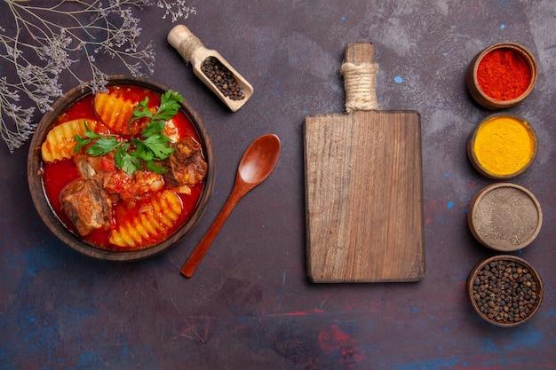 Bovenaanzicht smakelijke vleessoep met verschillende kruiden op zwart