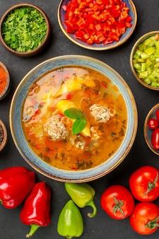 Bovenaanzicht smakelijke vleessoep met verse groenten op de donkere tafel