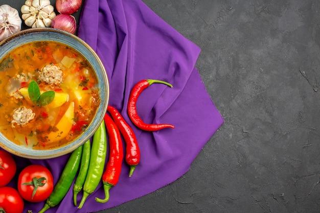 Bovenaanzicht smakelijke vleessoep met verse groenten op donkere tafel fotovoedselkleur