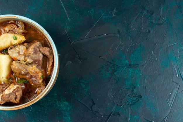 Bovenaanzicht smakelijke vleessoep met vleesaardappelen in plaat op het donkerblauwe bureau eten vlees groente diner calorie