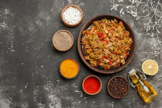 Bovenaanzicht smakelijke voedselkommen met kleurrijke kruiden, fles olie en citroen rond bruin bord met sperziebonen en tomaten naast de boomtakken