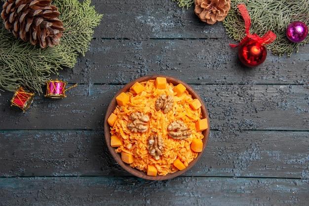 Bovenaanzicht smakelijke wortelsalade met walnoten op het donkerblauwe bureausalade noot gezondheidskleur voedseldieet