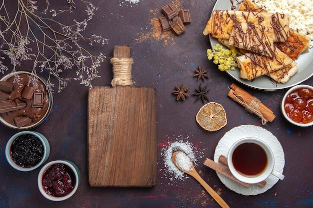 Bovenaanzicht smakelijke zoete gebakjes met kopje thee en jam op donkere achtergrond gebak koekjes cake suiker zoete thee
