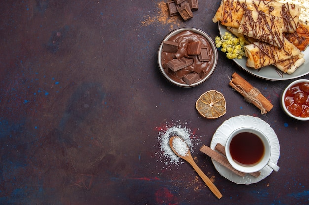 Bovenaanzicht smakelijke zoete gebakjes met kopje thee op donkere achtergrond gebak koekjes cake suiker zoete thee koekje