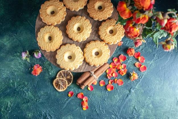 Bovenaanzicht smakelijke zoete koekjes op donkere achtergrond dessert biscuit suiker zoete pauze deeg thee cake taart bloem