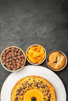 Bovenaanzicht smakelijke zoete taart met stukjes sinaasappel op donkere oppervlakte taart dessert thee zoete biscuit cake