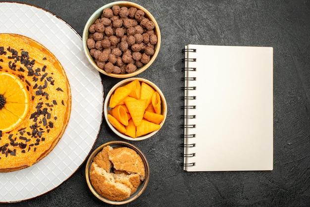 Bovenaanzicht smakelijke zoete taart met stukjes sinaasappel op donkere oppervlakte taart taart dessert thee biscuit