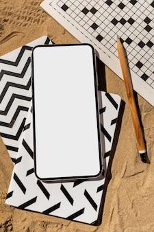 Bovenaanzicht smartphone en kruiswoordpuzzel Gratis Foto