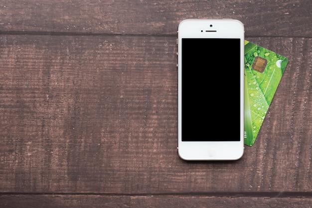 Bovenaanzicht smartphone met creditcard