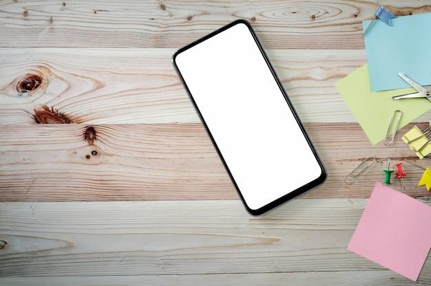 Bovenaanzicht smartphone met leeg scherm en benodigdheden op houten achtergrond, kopie ruimte.