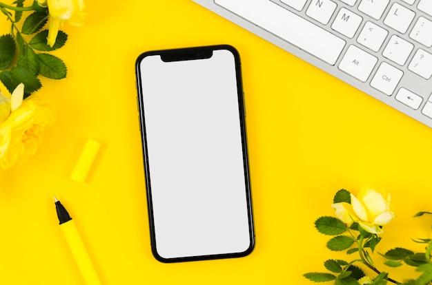 Bovenaanzicht smartphonemalplaatje over werkruimte