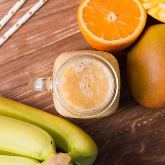 Bovenaanzicht smoothie pot met bananen en sinaasappel