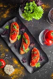 Bovenaanzicht snack met tomatensalade en gesneden brood en rucola in donkere plaat