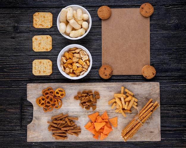 Bovenaanzicht snacks chocolade koekjes beschuiten mini brezel paprika chips cracker sticks viscrackers en maïs sticks op zwarte houten achtergrond