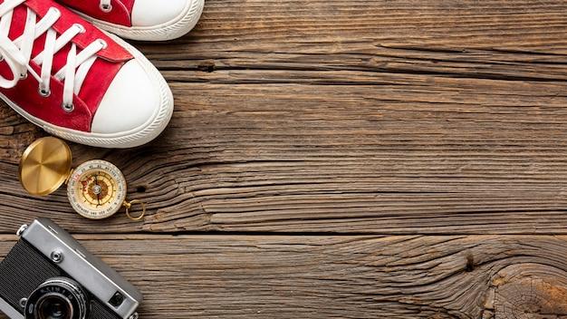Bovenaanzicht sneakers en kompas op een tafel