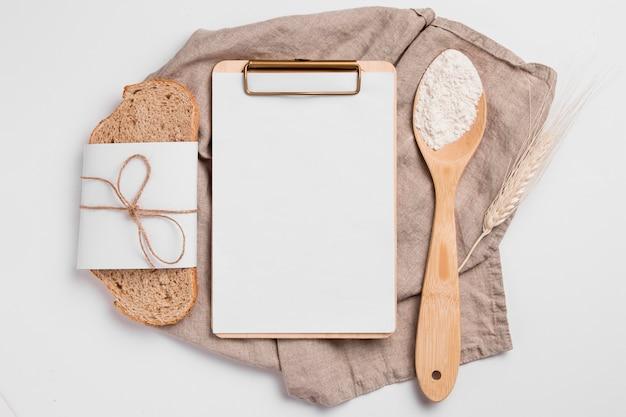Bovenaanzicht sneetje brood met leeg klembord en houten lepel