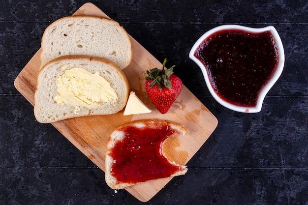 Bovenaanzicht sneetjes brood en boter met een sneetje brood met jam aan boord met aardbeien en jam in een schotel