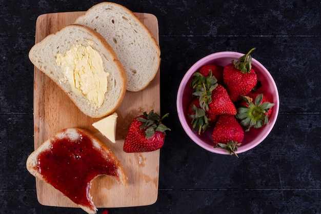 Bovenaanzicht sneetjes brood en boter met een sneetje brood met jam aan boord met aardbeien op de beker