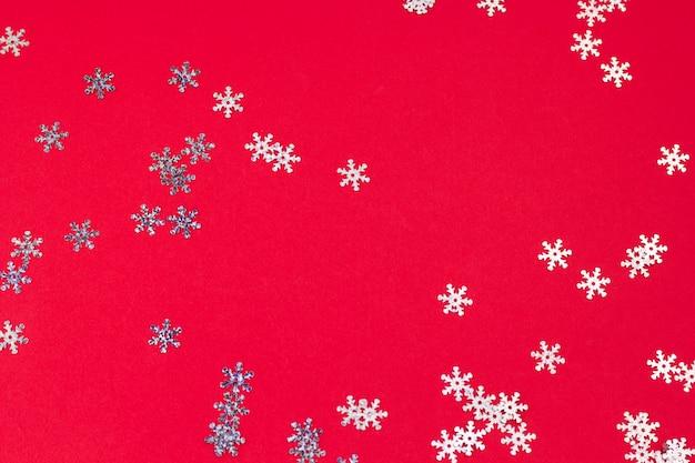 Bovenaanzicht sneeuwvlok confetti puinhoop op een rode achtergrond, abstracte feestelijke winter achtergrond