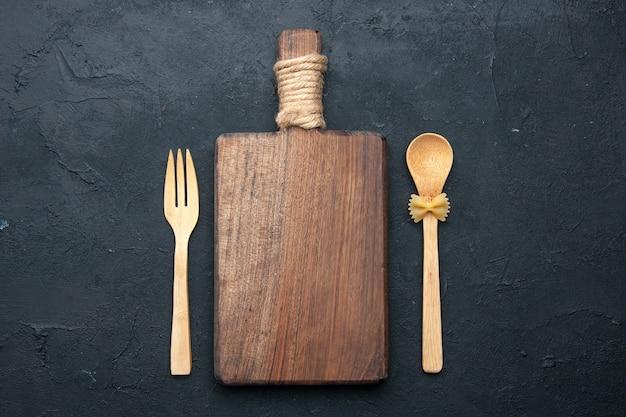 Bovenaanzicht snijplank houten lepel en vork op donkere ondergrond