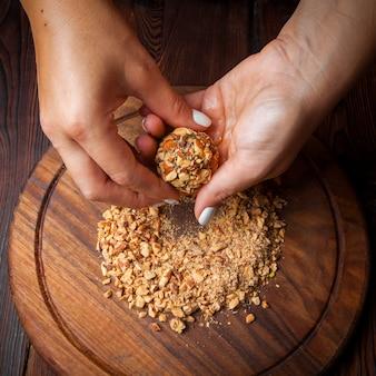 Bovenaanzicht snoep gemaakt met de hand zelfgemaakte snoepjes van noten, gedroogd fruit en honing op een donkere houten ondergrond