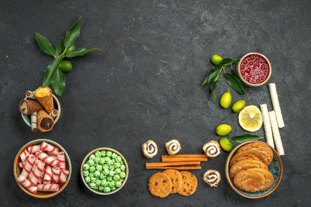 Bovenaanzicht snoep koekjes kleurrijke snoep wafels kaneel citrusvruchten met bladeren