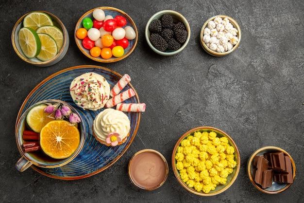 Bovenaanzicht snoep op tafel kommen van bessen chocolade citrusvruchten kleurrijke snoepjes en een bord cupcakes en een kopje kruidenthee met kaneelstokjes op de donkere tafel