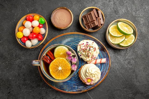 Bovenaanzicht snoep op tafel vier kommen chocoladesuikergoed en limoenen een bord met twee cupcakes en het kopje kruidenthee op tafel