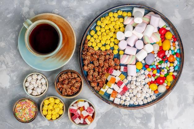 Bovenaanzicht snoep samenstelling verschillende gekleurde snoepjes met marshmallow en kopje thee op het lichte witte bureau suikerspin bonbon zoete confituur