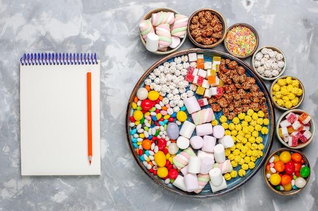Bovenaanzicht snoep samenstelling verschillende gekleurde snoepjes met marshmallow in potten met blocnote op wit bureau suikerspin bonbon zoete confiture