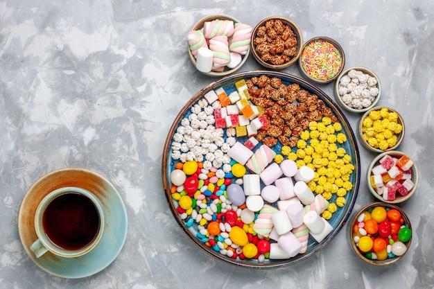 Bovenaanzicht snoep samenstelling verschillende gekleurde snoepjes met marshmallow in potten met thee op witte bureau suikerspin bonbon zoete confiture