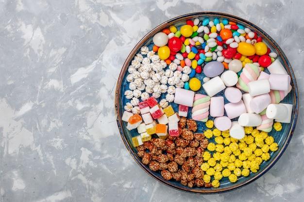 Bovenaanzicht snoep samenstelling verschillende gekleurde snoepjes met marshmallow op witte bureausuiker snoep bonbon zoete confitures