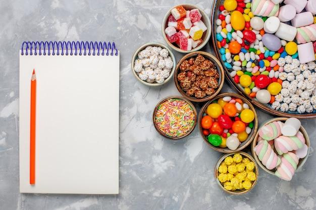 Bovenaanzicht snoep samenstelling zoete en heerlijke snoepjes met marshmallow op witte bureausuiker goodie confitures zoet