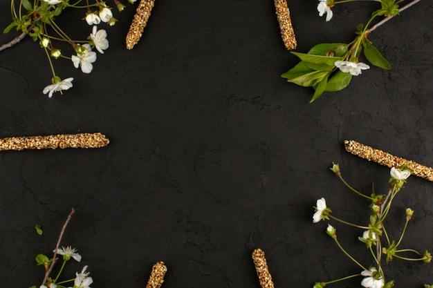Bovenaanzicht snoep steekt lekker samen met witte bloemen op het donkere bureau
